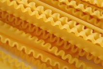 Background Close Up of Frilled Edges of Dry Lasagna Noodles - Arranged in Diagonal Pattern Across Frame